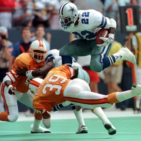 Dallas Cowboys running back Emmitt Smith (22) leaps over Tampa Bay Buccaneers free safety Harry Hamilton (39) as cornerback Ricky Reynolds (29) moves in on the play in Irving, Texas, on Oct. 7, 1990. (AP Photo/Ron Heflin)