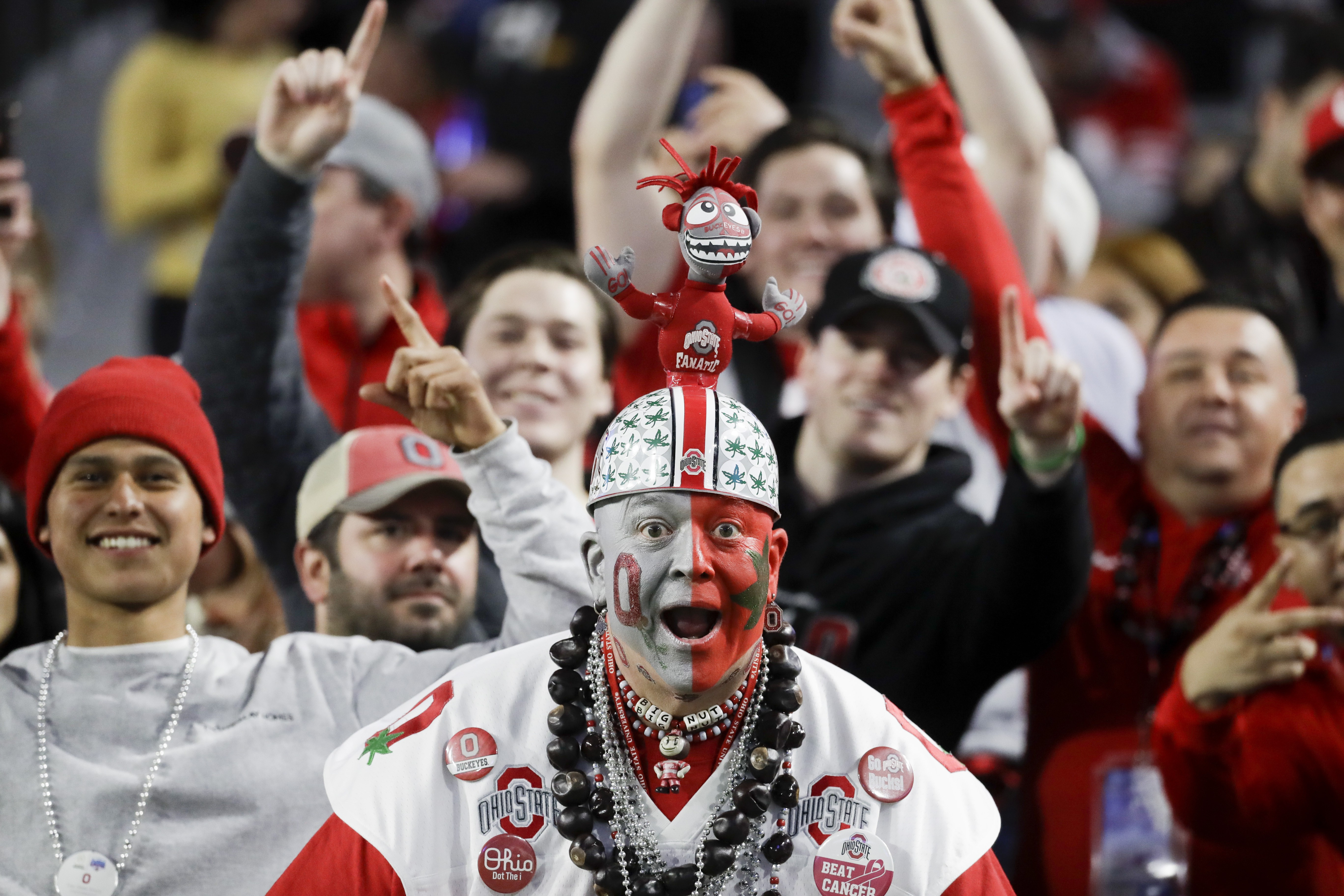 Am Ohio State fan watches players warm up for the Fiesta Bowl NCAA college football game between Ohio State and Clemson on Saturday, Dec. 28, 2019, in Glendale, Ariz. (AP Photo/Rick Scuteri)