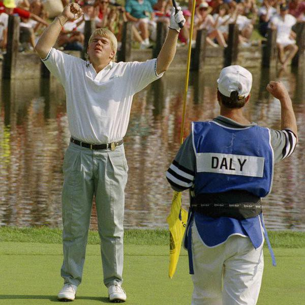 """ADVANCE FOR WEEKEND EDITIONS, AUG. 6-7 - FILE - This Aug. 11, 1991, file photo shows PGA champion John Daly celebrating with his caddy Jeff """"Squeaky"""" Medlin after winning the golf tournament in Carmel, Ind.   (AP Photo/Michael Conroy, File)"""