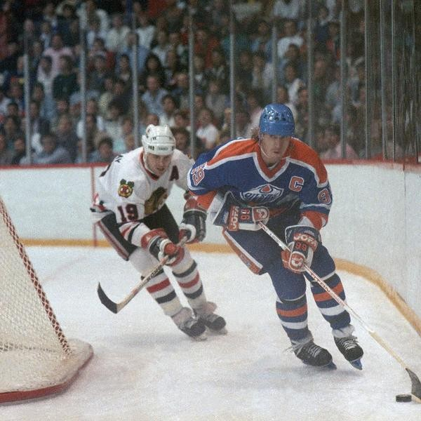 Edmonton Oilers' Wayne Gretzky (99) carries the puck behind the net while being followed by Chicago Black Hawks' Troy Myrray (19) in first period action, Sunday night, Nov. 15, 1987 in Chicago. (AP Photo/Fred Jewell)