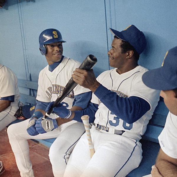 Ken Griffey, Jr., and Ken Griffey, Sr., kid around on the bench in Seattle during the Mariners' game against the Detroit Tigers, Aug. 31, 1990. Father and son wear the same uniform for the first time in Major League history. Ken Sr. joined the Mariners' club yesterday. Other players are not identified. (AP Photo/Bill Chan)